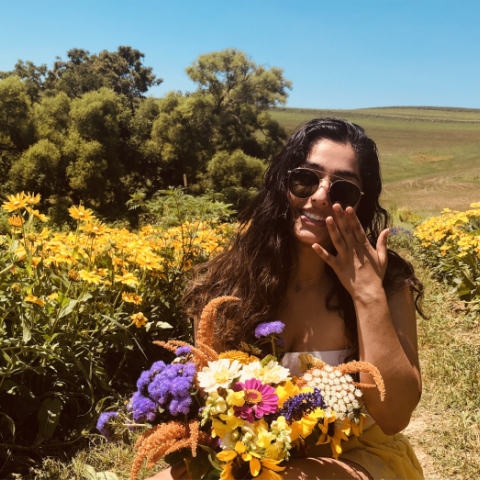 NHC PGH member Medha smiling in a field of flowers with sunglasses on and holding flowers