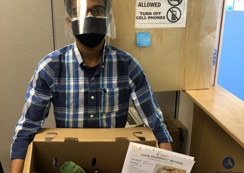 NHC SF Member Spencer Robinson holding a box of produce and a recipe for patients at Food Pharmacy.