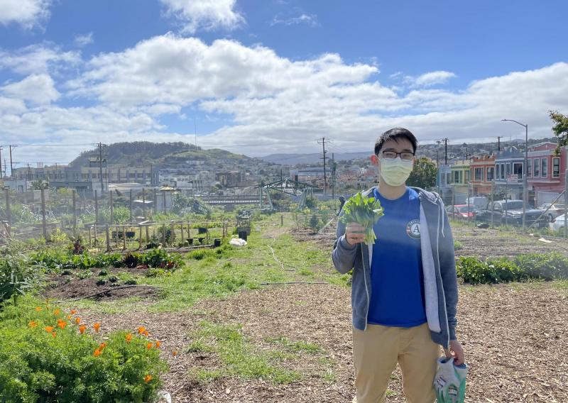 NHC SF member Jacky Chu holding a plant in their right hand. The background is a garden with semi-cloudy blue skies overhead.