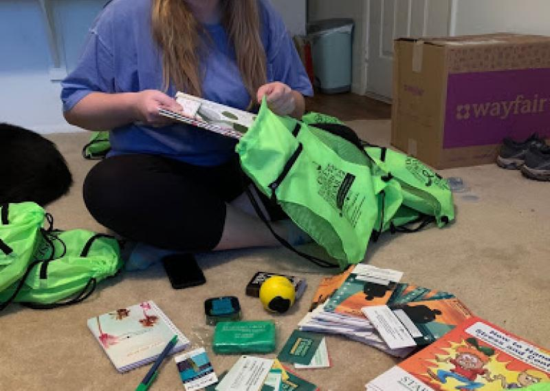 NHC member Paige sitting on the floor filling green bags with items called wellness kits