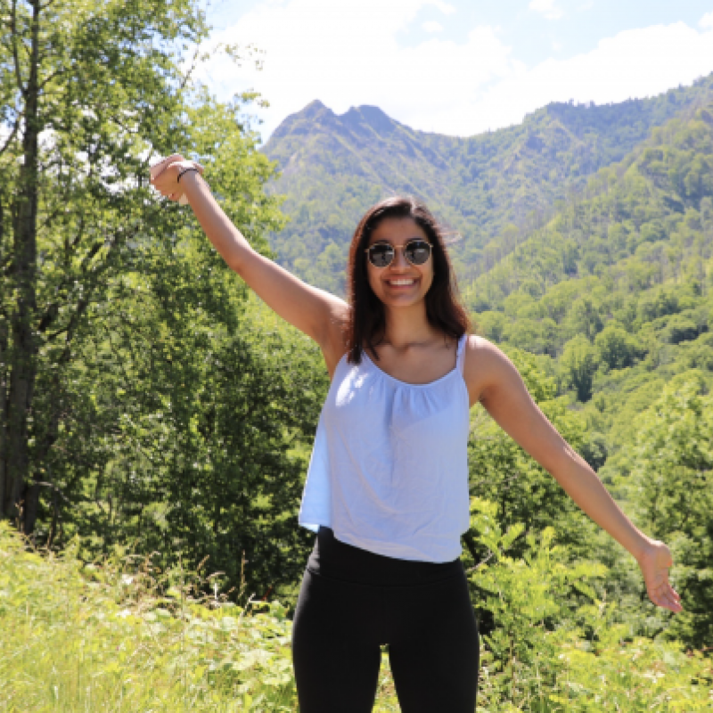 NHC PGH member Geeta smiling and holding her arms diagonal with sunglasses on and a mountain in the background