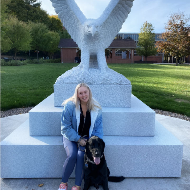 NHC PGH member Laurel smiling in front of a statue with her dog